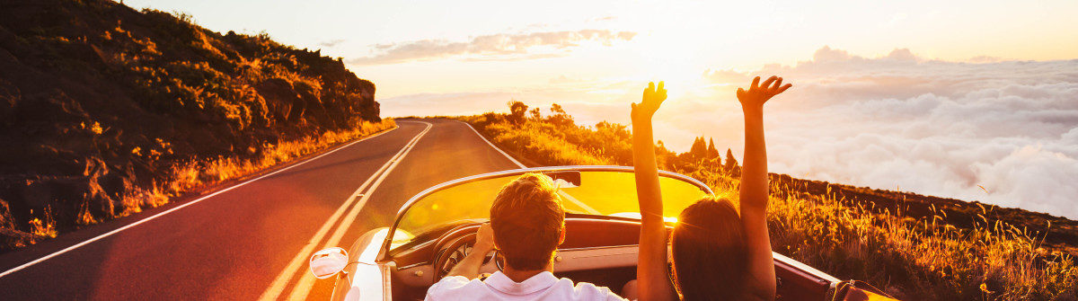 happy-couple-driving-on-country-road-into-the-sunset-in-classic-vintage-sports-car-shutterstock_305567459-2-1200×335