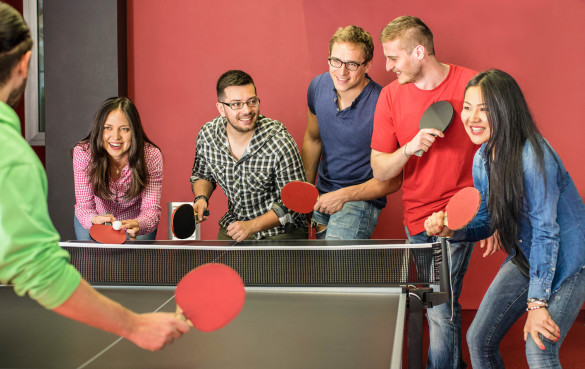 group-of-happy-young-friends-playing-ping-pong-table-tennis-shutterstock_270733406-2-1-585x369