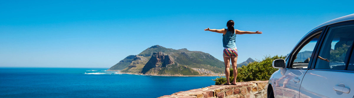 carefree-tourist-stands-on-chapmans-peak-drive-shutterstock_126991940-2-1200×335