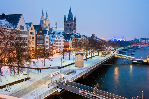 Cologne, Germany - February 14, 2010. Cologne's Old Town in winter time. View from the Deutz bridge. The pedestrian promenade with the cruise ship jetties in front. In the background the church Great Saint Martin (Groß St. Martin) and the Cologne Cathedral.