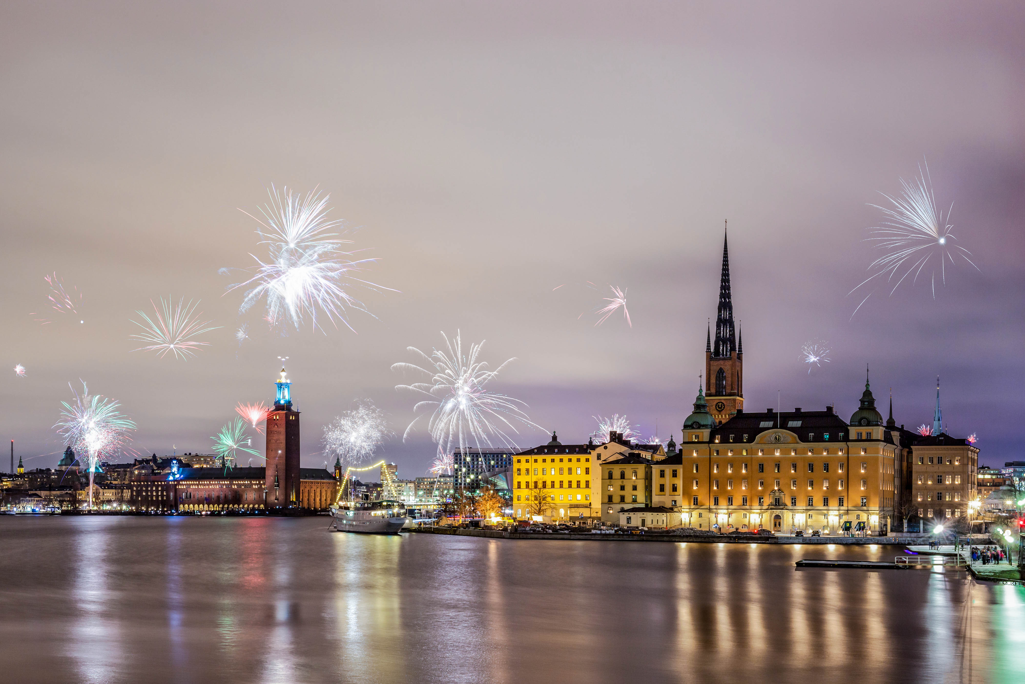 Stockholm, Sweden – Jan 1, 2016: New Year Fireworks are popping across Stockholm main islands and city hall on Jan 1 in Stockholm. On New Year's Eve, Stockholm's streets are filled with families, friends and lovers with fireworks and champagne in their hands.