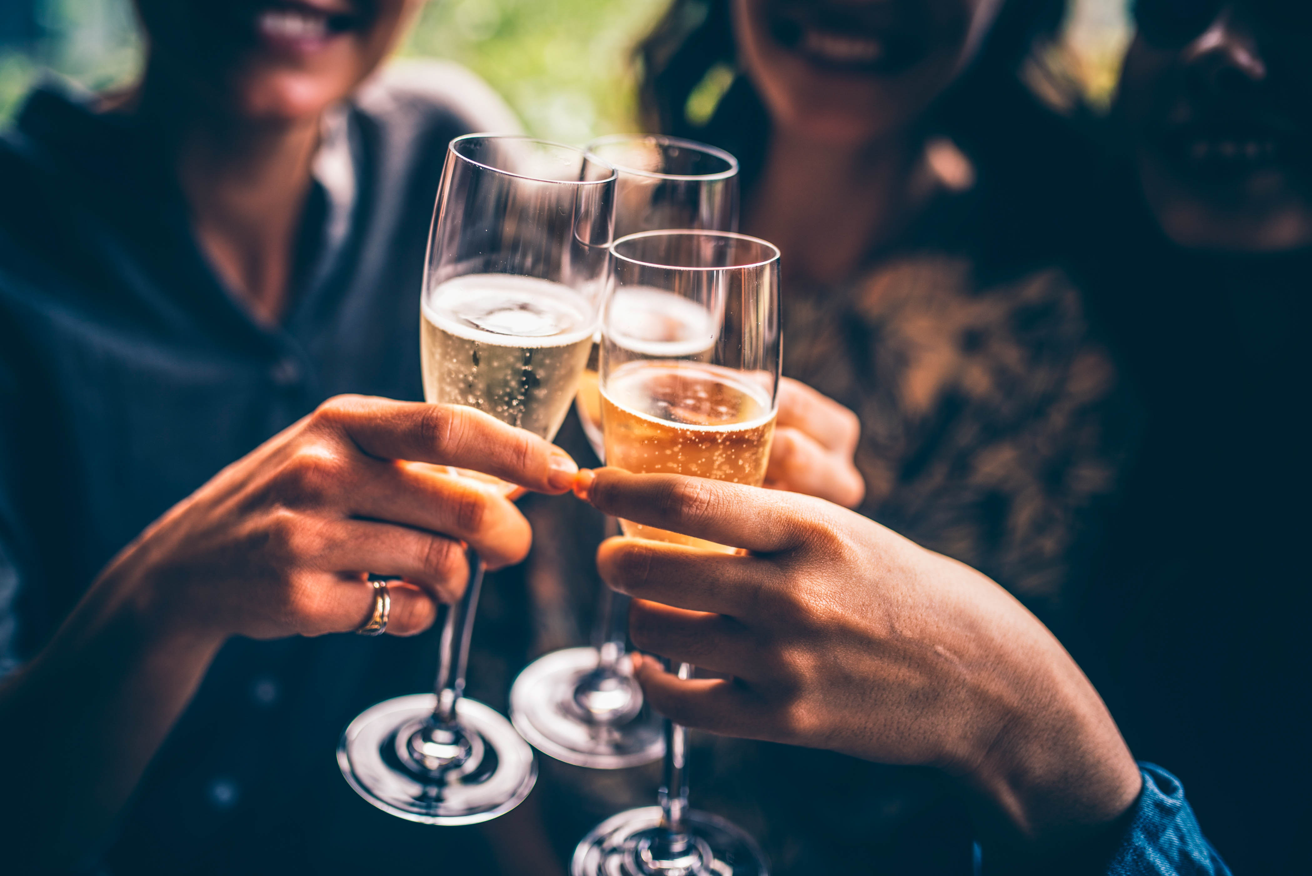 Three female friends celebrating with champagne. They are sitting in a bar and toasting with glasses of champagne.