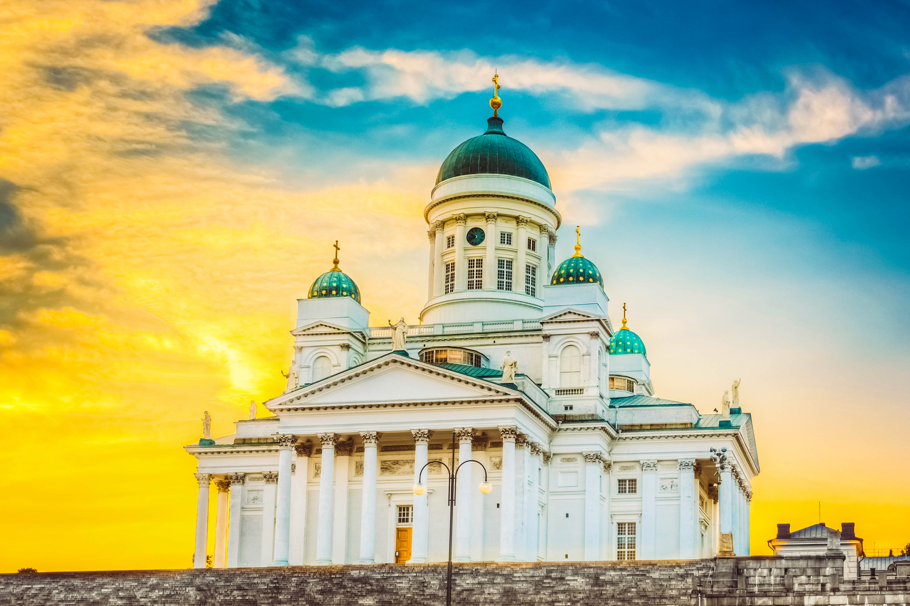 Famous Landmark In Finnish Capital: Senate Square With Lutheran Cathedral And Monument To Russian Emperor Alexander Ii At Summer Sunset Evening With Dramatic Sky