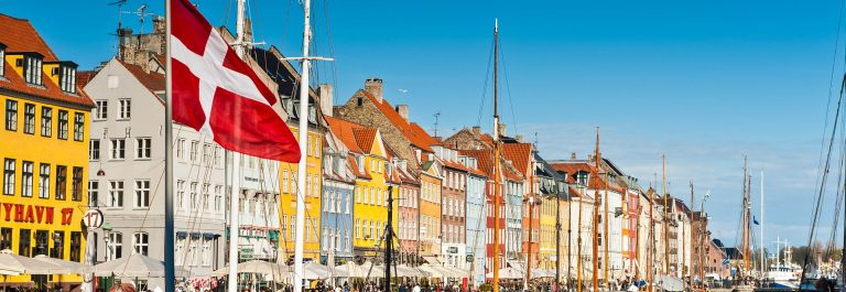 Copenhagen Danish flag flying over Nyhavn colourful harbour