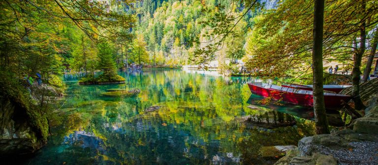 yellow-leaves-and-red-boat-at-blausee-blue-lake-nature-park-kandersteg-switzerland-shutterstock_127214768-2