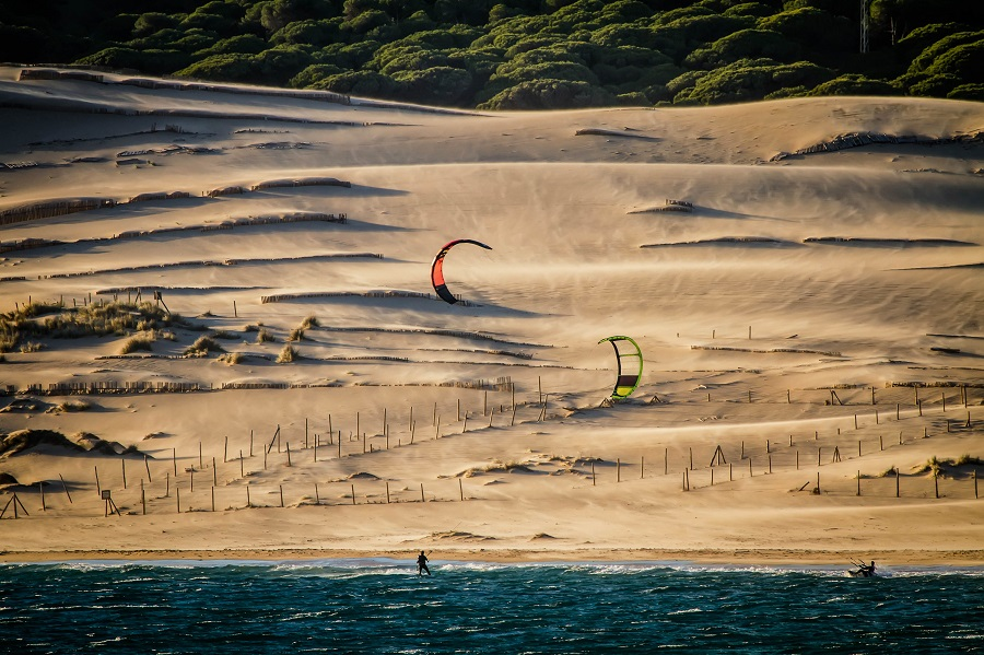Andalusien, kiters are riding in front of sand dunes