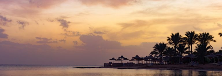 Beautiful-sunrise-on-the-beach-in-Egypt-Marsa-Alam.-Beach-sea-beautiful-sky-and-beach-umbrellas-at-sunrise_shutterstock_572960305_1920