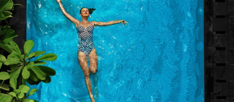 Woman Relaxing In Swimming Pool Water. Summer Holidays Vacation.