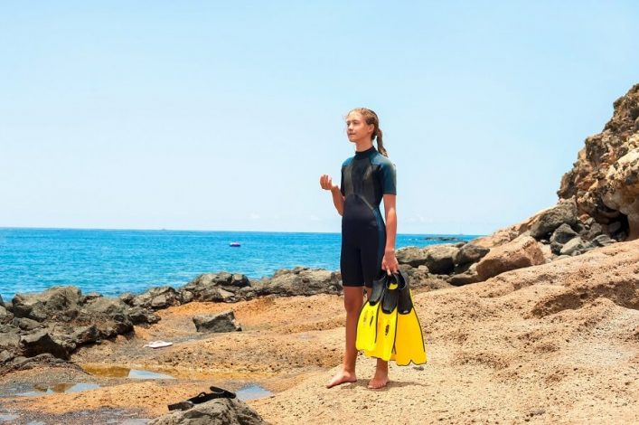 Young-lady-in-diving-suit-with-paddles-standing-on-Atlantic-ocean-rock-coast.-Tenerife-Canary-islands-Spain-shutterstock_3095923341