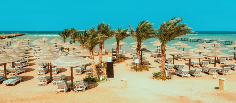 Chaise lounge and parasols on the beach against the blue sky and sea. Egypt, Hurghada