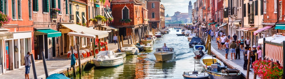 Island-murano-in-Venice-Italy.-View-on-canal-with-boat-and-motorboat-water.-Picturesque-landscape._720444505