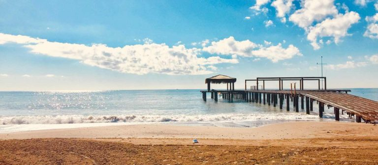 View-of-the-sea-and-pier-at-sunset-wide-beach-blue-sky-and-wonderful-clouds-in-Belek-Antalya_shutterstock_1010229820