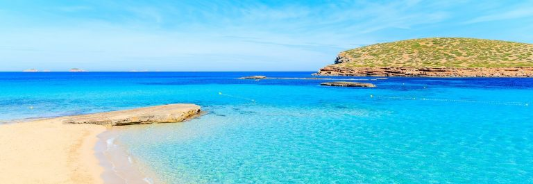Beautiful-sandy-Cala-Comte-beach-with-azure-blue-sea-water-Ibiza-island-Spain-shutterstock_650392843-tiny