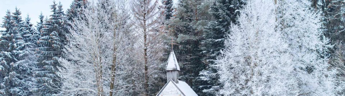 Small-wooden-chapel-on-snowbound-frosty-glade-in-snowy-frozen-forest.-Winter-wonderful-scenery-in-German-Bavarian-region-Allgaeu_shutterstock_516979453