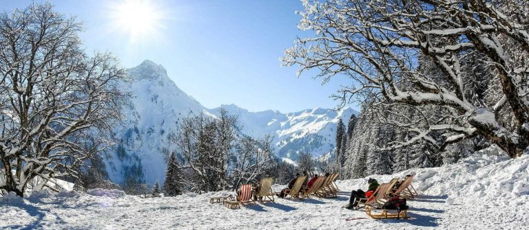 Group-of-people-sitting-with-deck-chairs-in-winter-mountains.-Sunbathing-in-snow.-Germany-Bavaria-Allgau-Schwarzenberghuette_shutterstock_771046954-1