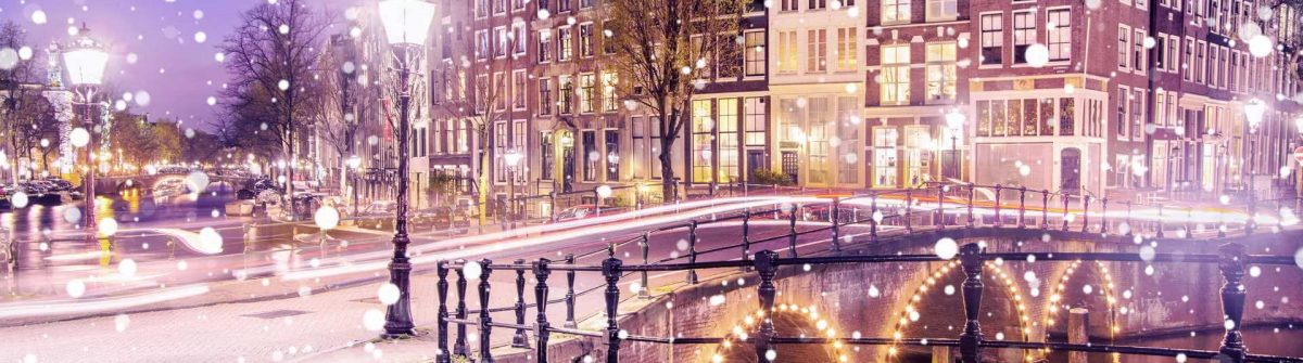Traditional-Dutch-old-houses-and-bridges-on-the-canals-in-Amsterdam-on-a-snowy-winter-night-The-Netherlands-shutterstock_749536627