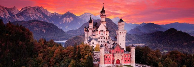 Neuschwanstein-fairy-tale-castle.-Beautiful-sunset-view-of-the-bloody-clouds-with-autumn-colours-in-trees-twilight-night-Bavarian-Alps_shutterstock_1030422793
