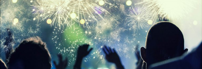 Cheering crowd and fireworks at New Year's Eve – people celbrating on open air