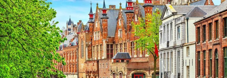 Medieval-town-Bruges-in-Belgium.-Panorama-and-landscape-vintage-channel-with-old-brick-house-broach-on-roof.-Spring-sunny-day-blue-sky-white-cloud-end-green-trees._650360299_1920x1280