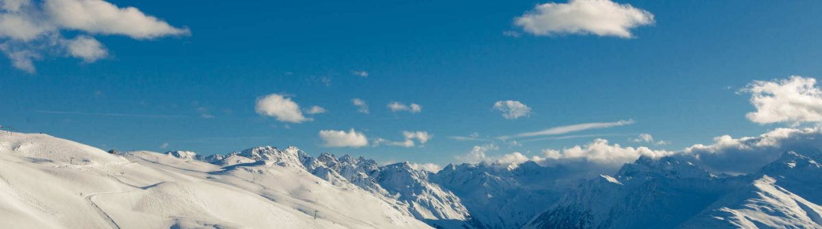 Ski-run-Davos-Switzerland-sunny-snowy-landscape-with-panoramic-view_shutterstock_1311050099