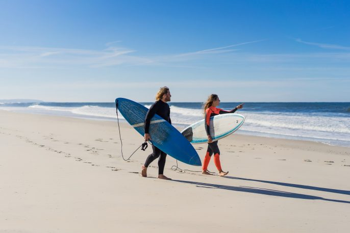 Man,And,Woman,Go,To,The,Ocean,With,Surf,Boards.